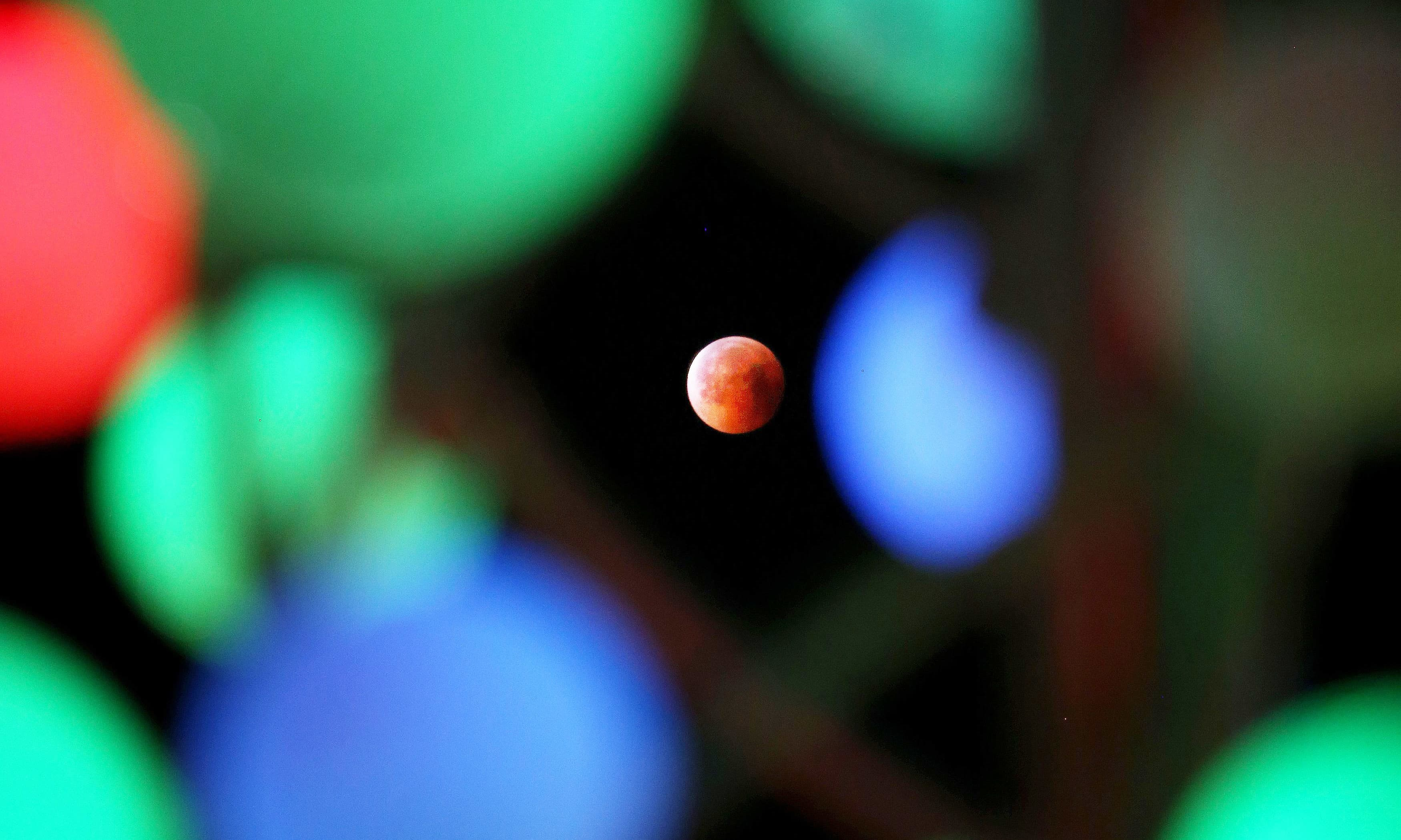 "A picture taken on July 27, 2018 shows the moon during the total lunar eclipse, also known as the ""blood moon"", taken as it passes through derorative lights in Kuwait City. — AFP"