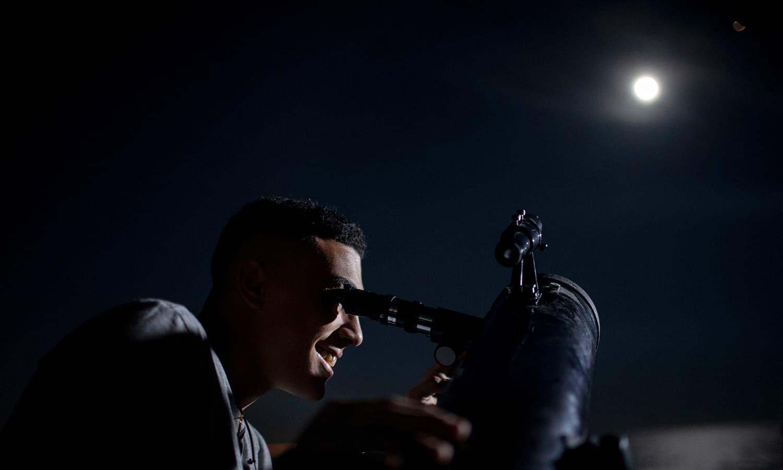 A man looks at the moon eclipse through a telescope over Copacabana Fortress in Rio de Janeiro, Brazil. — AFP