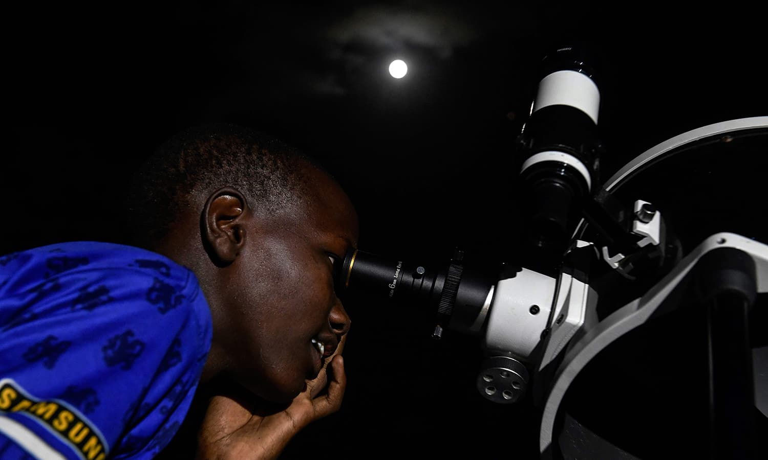 """A man looks through a telescope at a """"blood moon"""" eclipse in Oloika town in Magadi, Kenya. — AFP"""