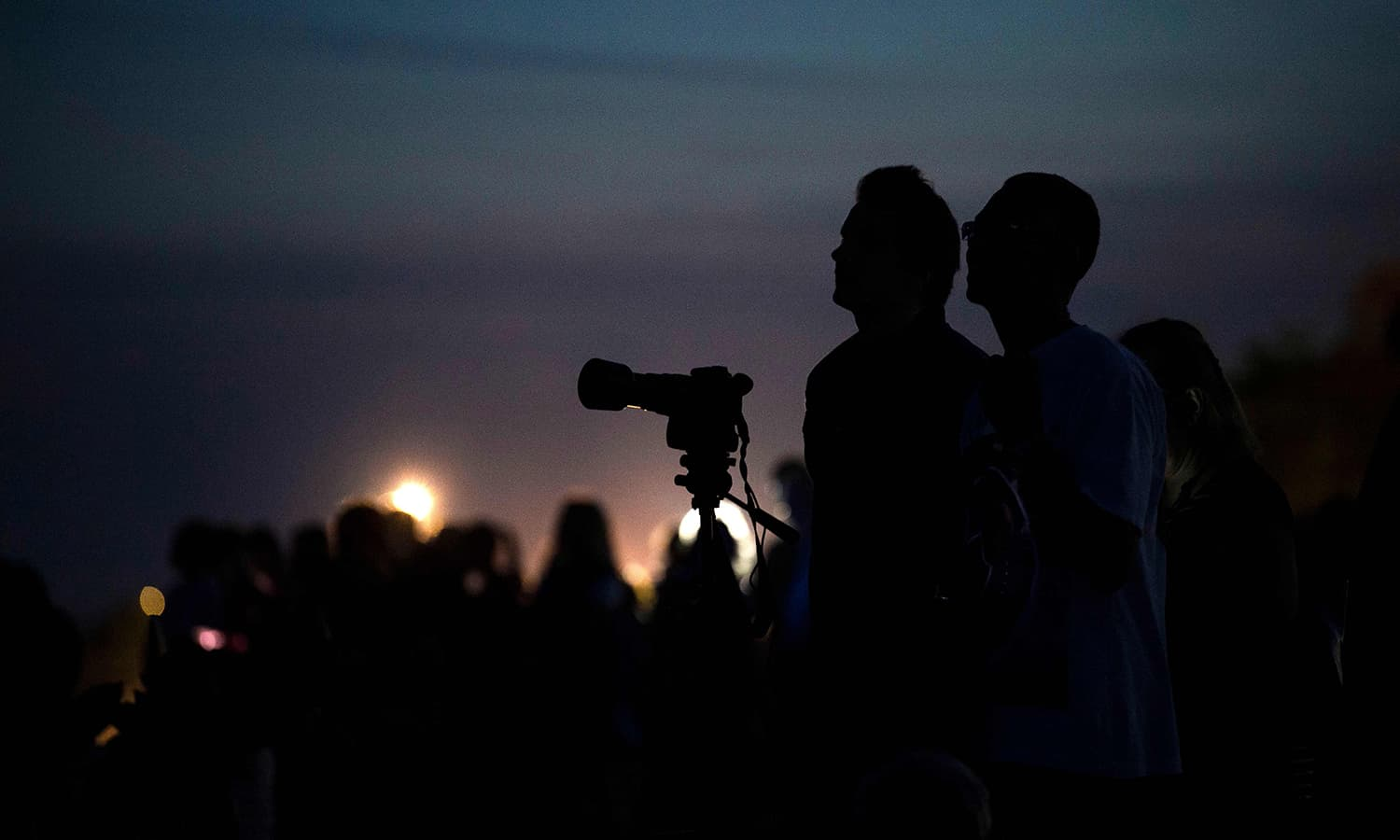 Men take pictures of the moon eclipse at Copacabana Fortress in Rio de Janeiro, Brazil. — AFP