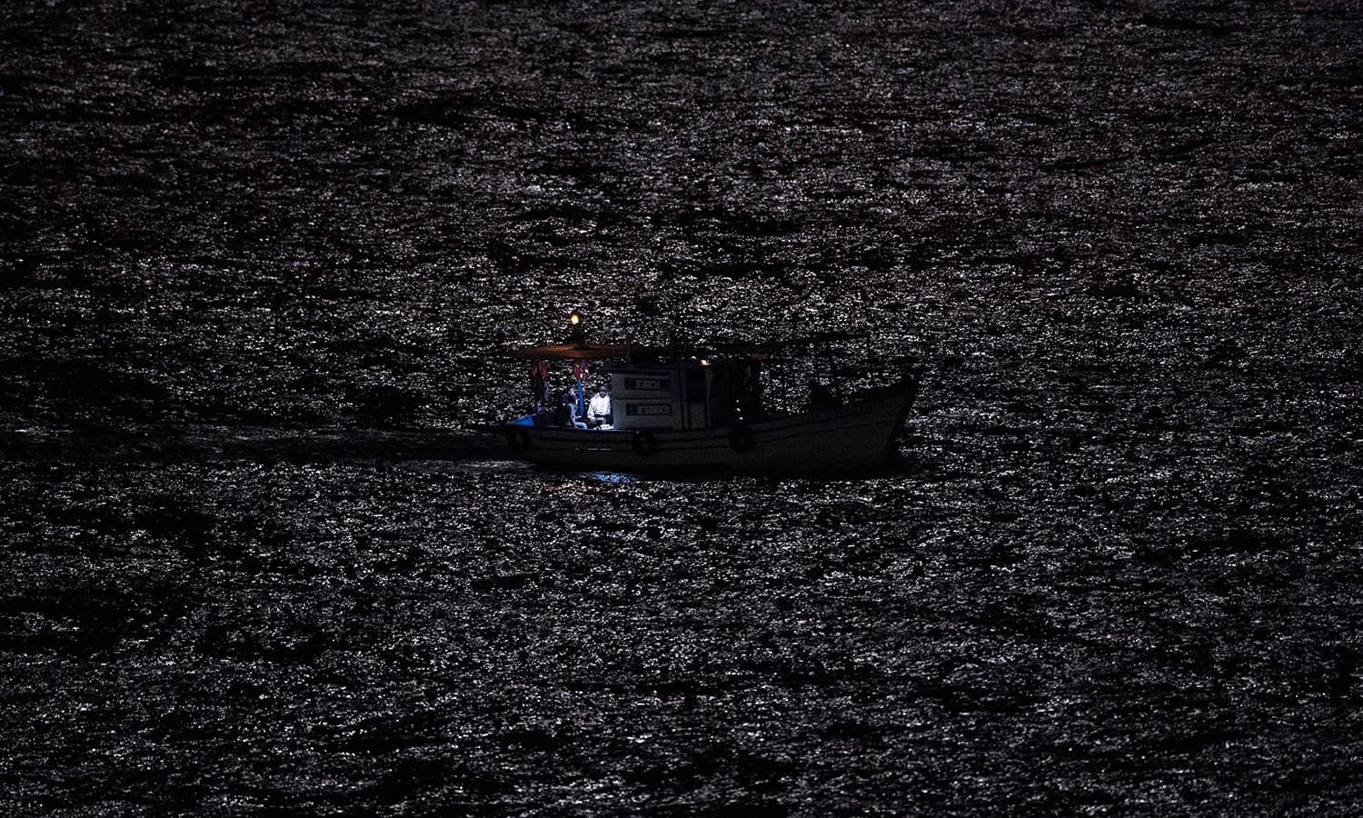 A fishermen boat crosses the reflection of the moonlight during the moon eclipse in Rio de Janeiro Brazil. — AFP