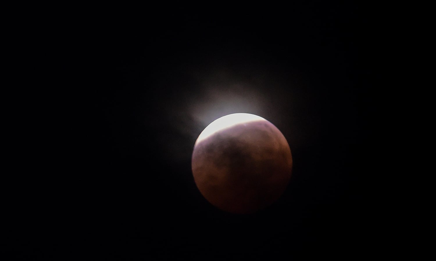 """This picture shows the full moon during a """"blood moon"""" eclipse as seen from Dhaka, Bangladesh. — AFP"""