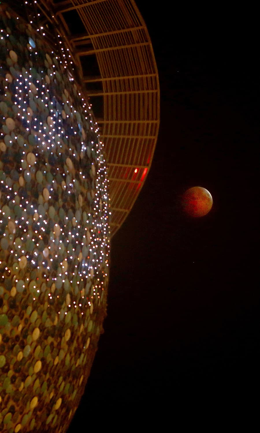"""Picture shows the moon during the total lunar eclipse, also known as the """"blood moon"""", taken as it passes by Kuwait Towers in Kuwait City. — AFP"""