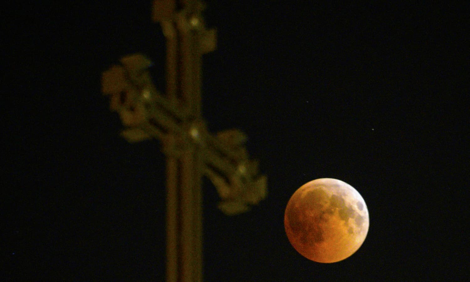 """A picture taken early on July 28, 2018, shows the moon during the total lunar eclipse, also known as the """"blood moon"""", taken as it passes over an Armenian Apostolic Church cathedral in Yerevan. — AFP"""