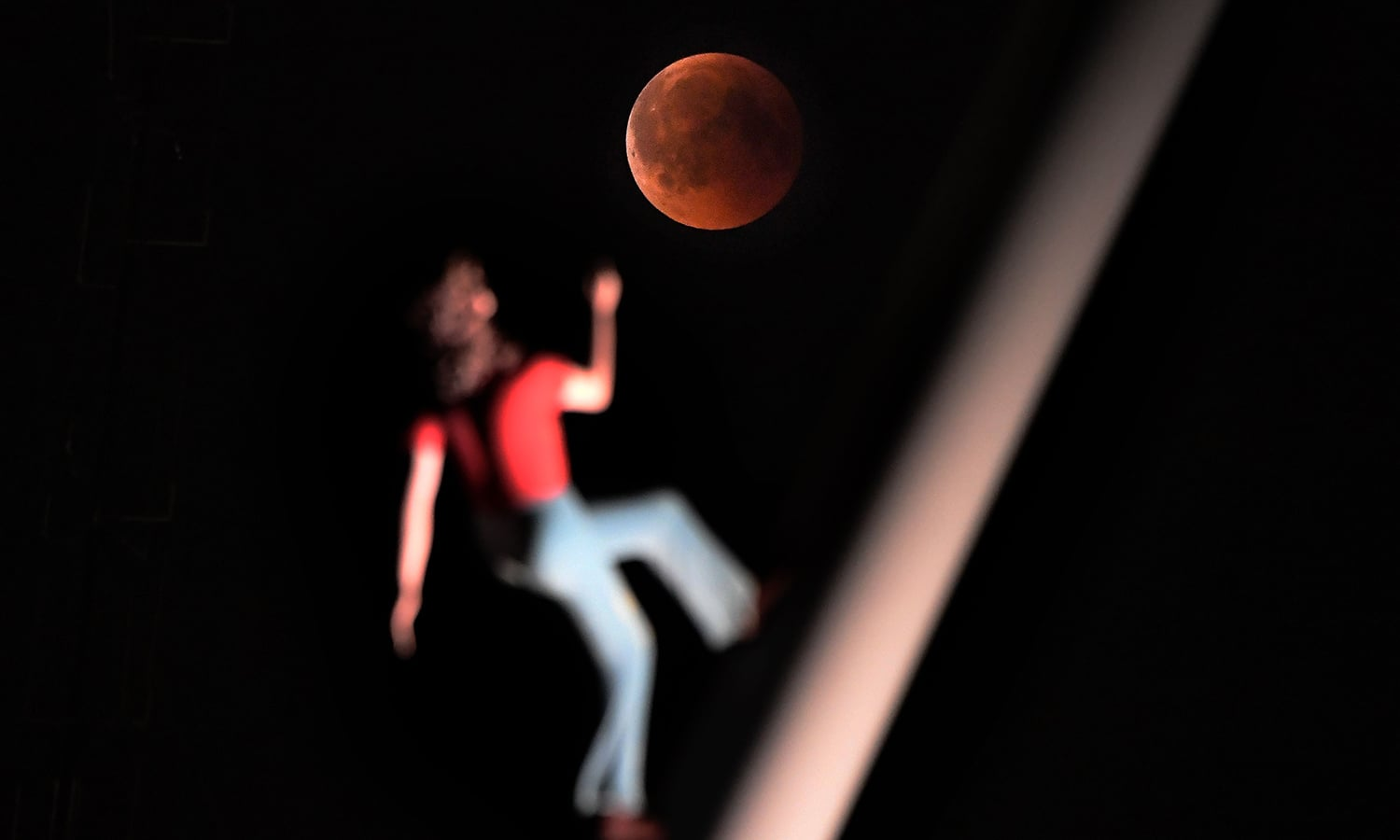 """A """"blood moon"""" eclipse is pictured with a sculpture by the American artist Jonathan Borofsky """"Woman walking to the sky"""" in Strasbourg, eastern France. — AFP"""