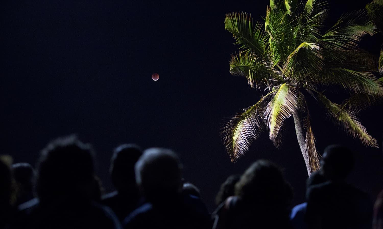 People watch the blood moon rising at Arpoador beach in Rio de Janeiro, Brazil. — AP