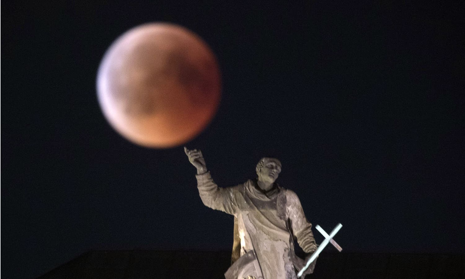 The moon turns red during a total lunar eclipse, as seen from Dresden, Germany. — AP
