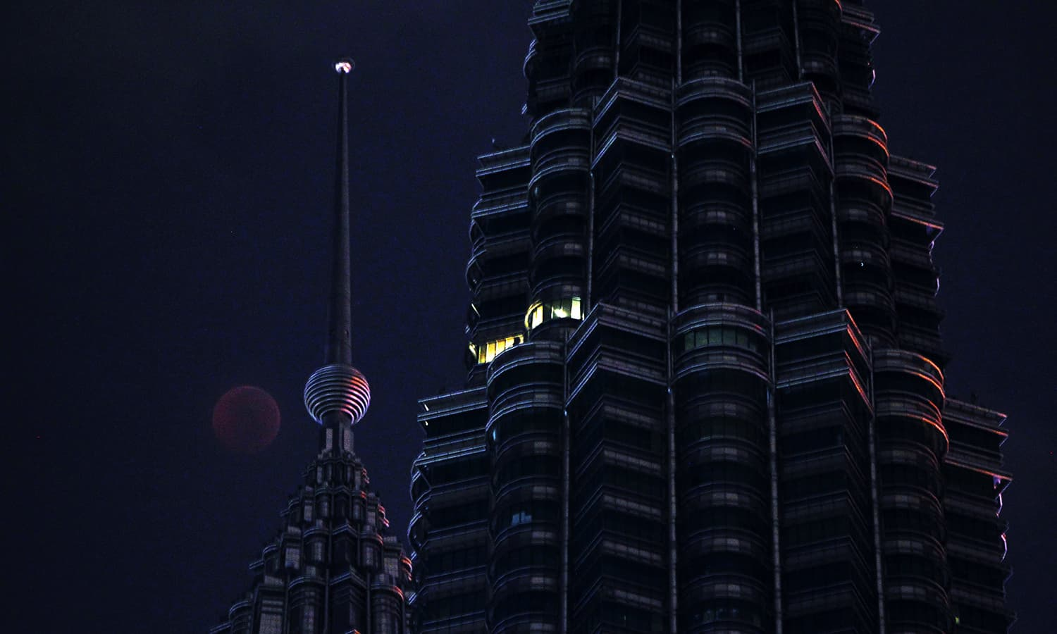 A full moon sets over Petronas Twin Tower during a complete lunar eclipse in Kuala Lumpur, Malaysia. — AP