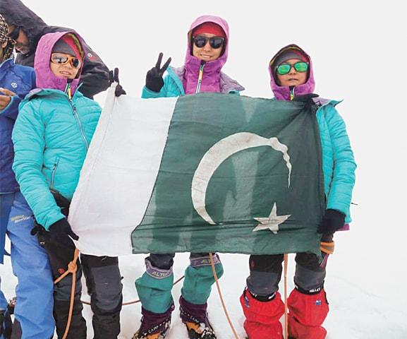 Amina Hanif, Maryam Bashir and Siddiqa Batool hold the Pakistani flag after scaling Manglesser peak.—Dawn