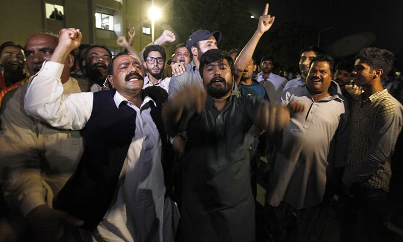 Supporters of ex-PM Nawaz Sharif chant slogans outside the cardiac ward of Pims on Sunday. — AP