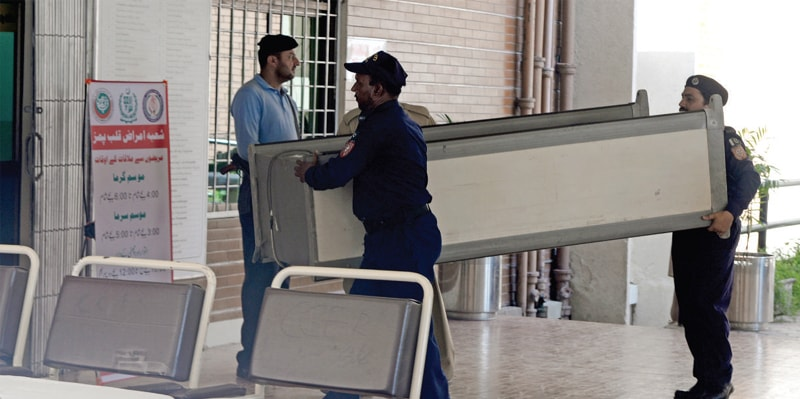 Security officials carry a walkthrough gate to install at the entrance of the cardiology emergency at Pims on Sunday. — White Star