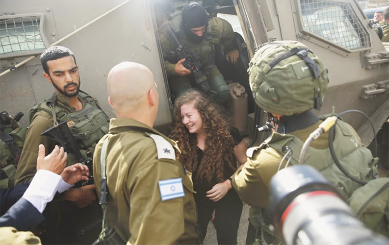 "AHED Tamimi leaves an armoured military vehicle after her release from an Israeli prison upon completion of an eight-month sentence on Sunday. Tamimi was jailed for slapping Israeli soldiers last year, an episode that made her a symbol of resistance for Palestinians. ""The resistance continues until the fall of the occupation,"" she said at a press conference in her village.—AP"