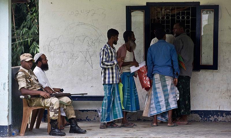 بھارت کے گوہاٹی گاؤں میں مسلمان افراد قومی رجسٹر برائے شہریت میں اپنا نام تلاش کر رہے ہیں — فوٹو: اے پی