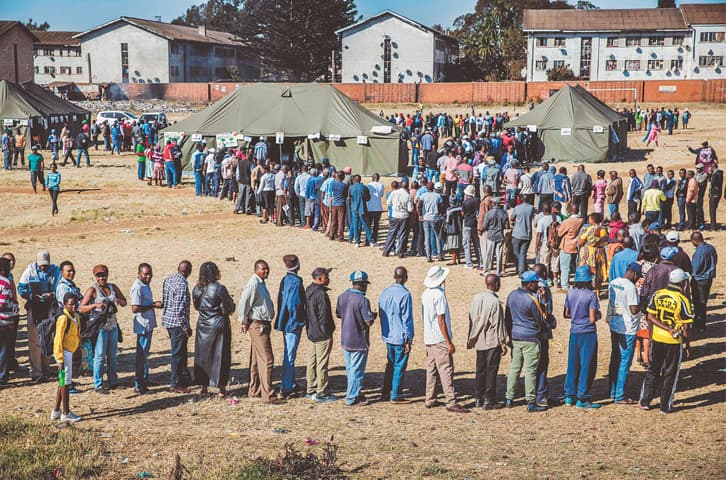 Harare: People queue in order to cast their ballot outside a polling station.—AFP