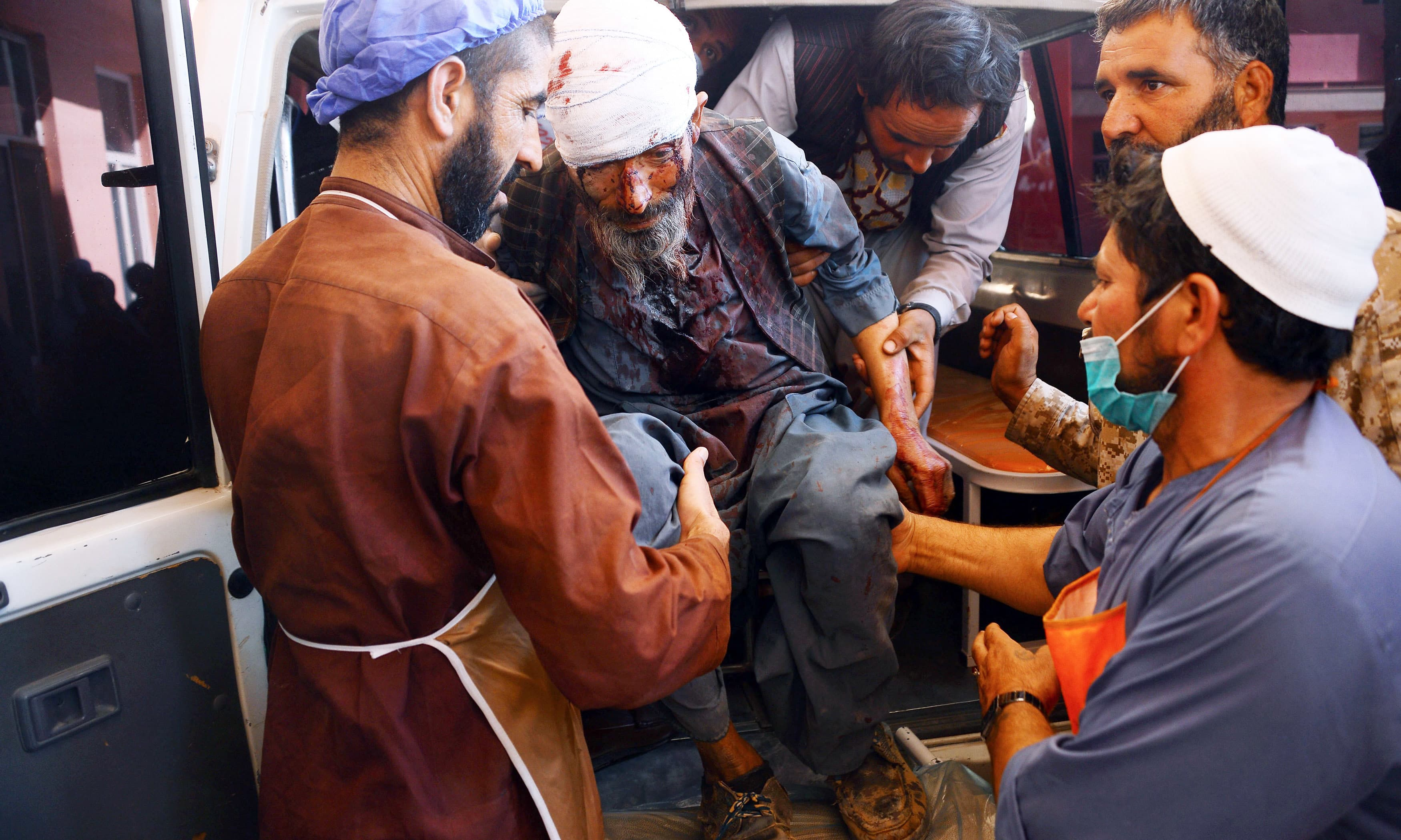 A wounded Afghan man is brought to a hospital after roadside bomb hit a passenger bus in Herat. —AFP