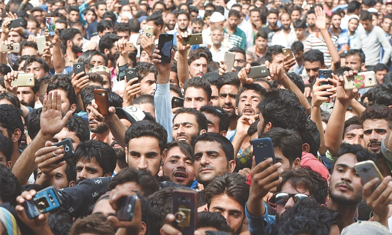 THIS file photo taken on Aug 1, 2017, shows Kashmiri villagers using smartphones to take pictures of a martyred militant during his funeral in Lelhar village in Pulwama, south of Srinagar.—AFP