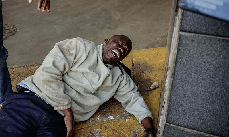 An injured man reacts as soldiers disperse demonstrators in Harare. — AFP