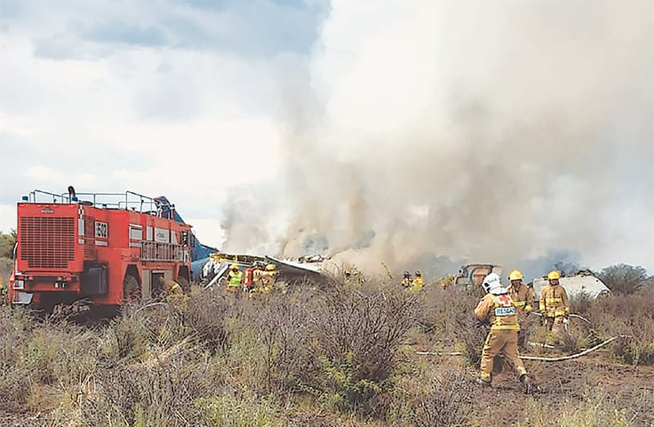 Firemen working as smoke billows from the wreckage of a plane that crashed with 97 passengers and four crew on board on take off at the airport of Durango in northern Mexico on Wednesday.—AFP
