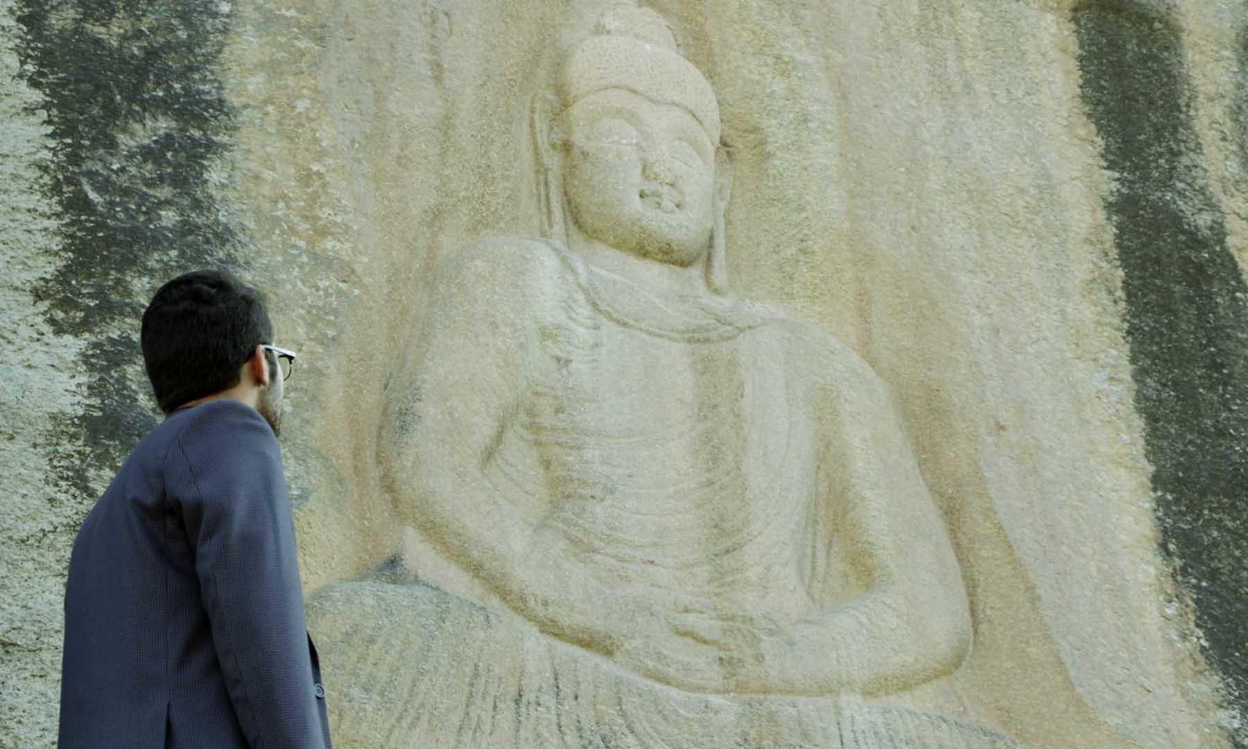 ایک مقامی سیاح بدھا کے مطمئن چہرے کا نظارہ کر رہا ہے—امجد علی سحاب