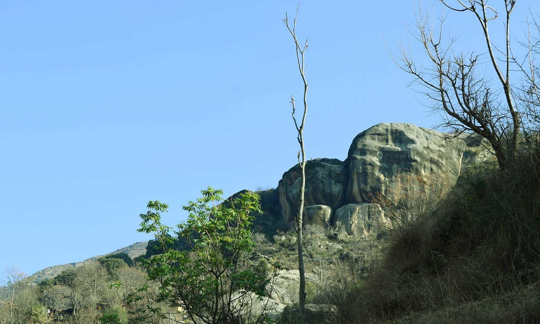 پہاڑی پر موجود بڑے پتھروں پر بدھا کا مجسمہ دکھائی دے رہا ہے—تصویر امجد علی سحاب