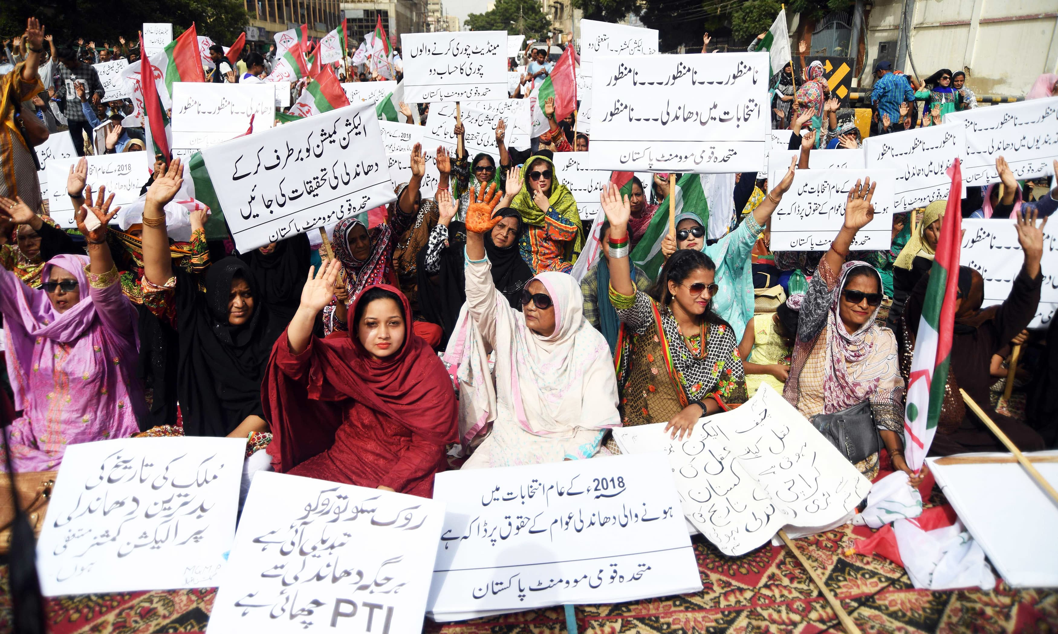MQM supporters carry placards as they chant slogans during a protest against alleged election rigging in Karachi. —AFP