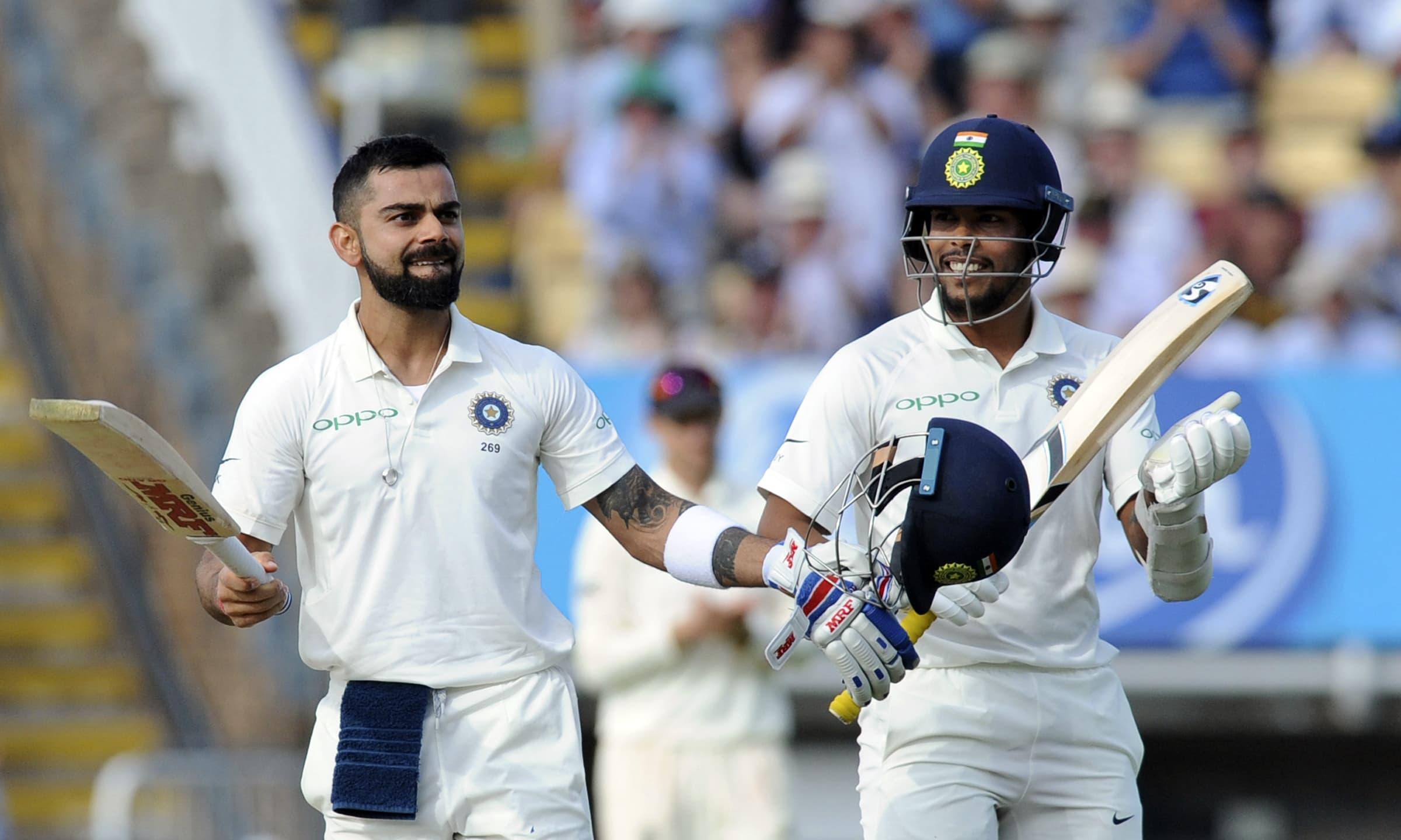 Virat Kohli celebrates after scoring a century, applauded by teammate Umesh Yadav. —AP