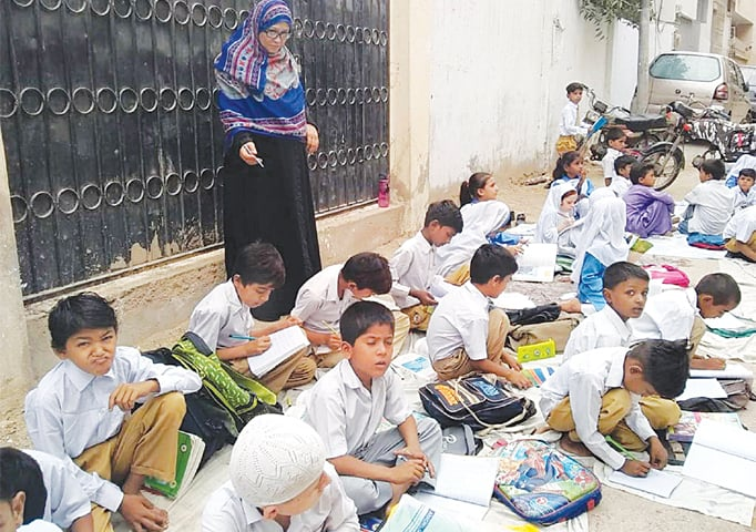 Students of the government school in Gulshan-i-Iqbal study outside on the footpath after they were prevented from entering it on Thursday.—PPI