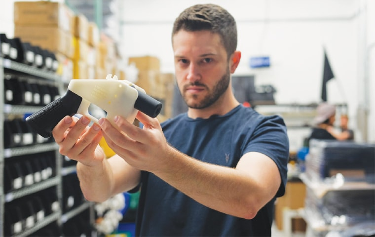 "Cody Wilson holds a 3D-printed gun, called the ""Liberator"", at his factory in Austin, Texas.—AFP"