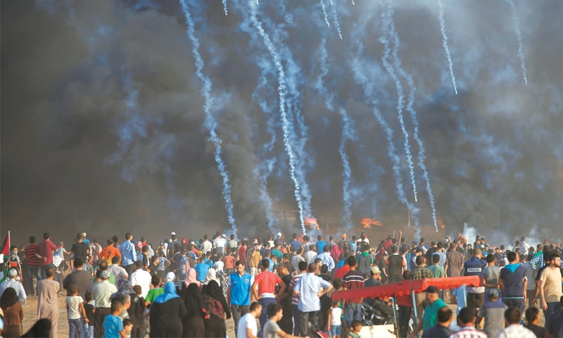 Tear gas canisters are fired by Israeli troops towards Palestinian demonstrators during a protest demanding the right to return to their homeland at the Israel-Gaza border on Friday.—Reuters