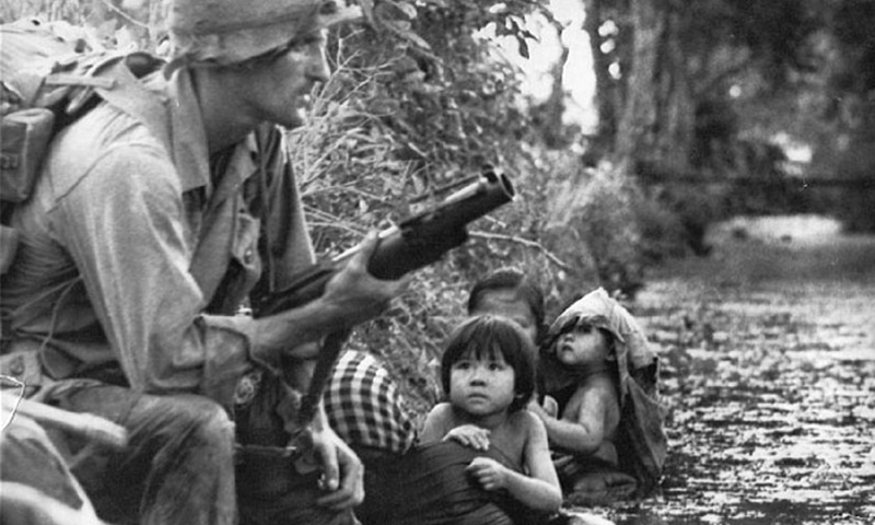 An American soldier with M79 grenade launcher helping civilians take cover from a Viet Cong sniper in a canal near Bao Trai | Imgur.com