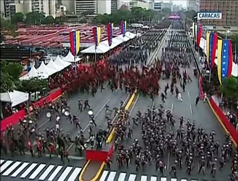 Screengrab taken from a handout video released by Venezuelan Television (VTV) showing uniformed military members breaking ranks and scattering after a loud bang was heard during a ceremony to celebrate the 81st anniversary of the National Guard in Caracas on August 4, 2018. ─ AFP