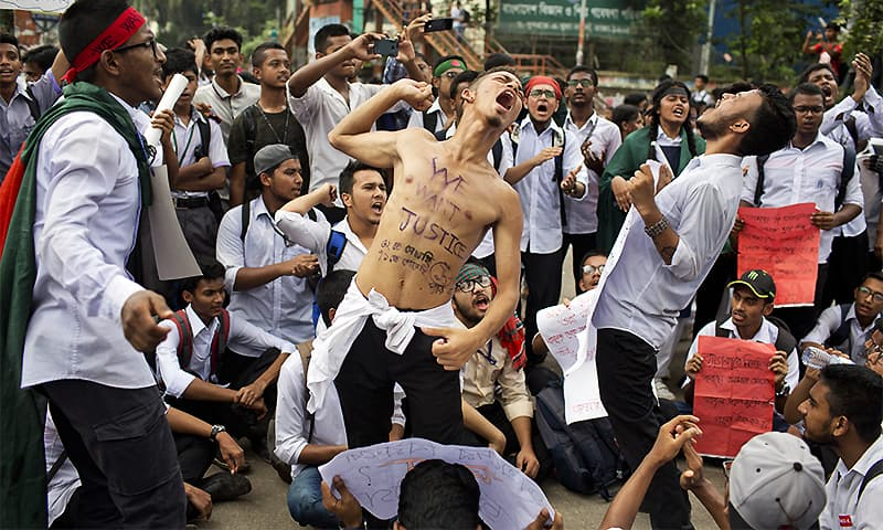 Bangladeshi students shout slogans and block a road during a protest in Dhaka. ─ AP