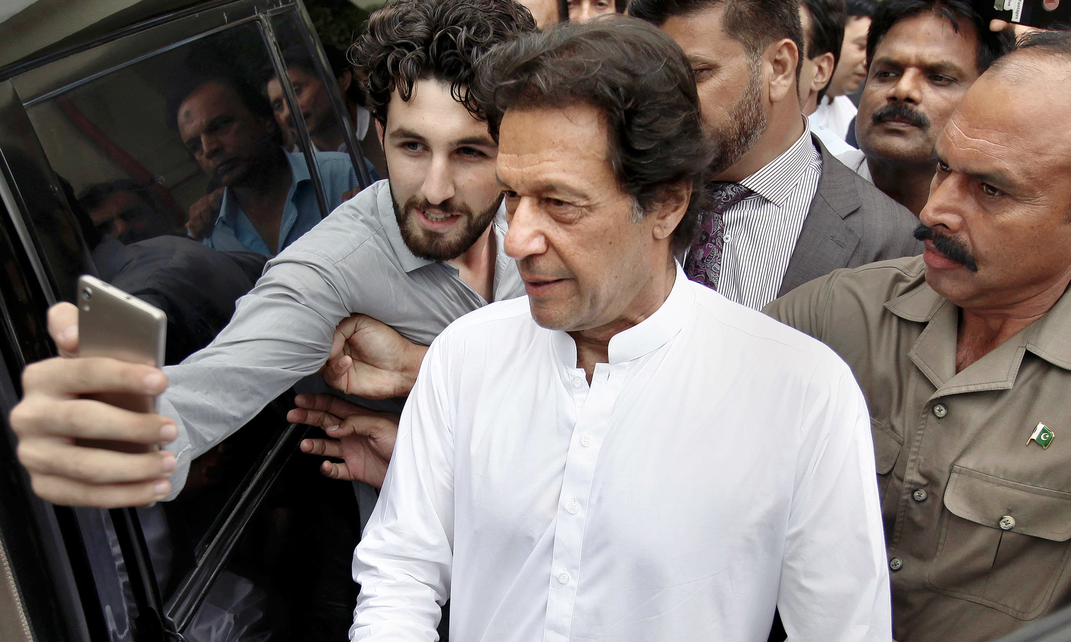 A man takes selfie with Imran Khan following a party meeting in Islamabad. —AP