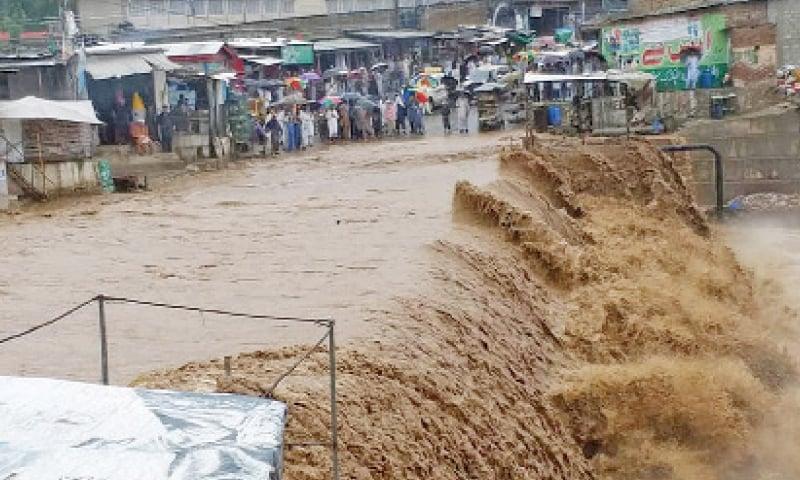Flash flood in a stream at Talash, Lower Dir, disrupted traffic on Timergara-Peshawar Road for hours on Wednesday. — Dawn