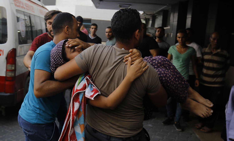بمباری سے زخمی ہونے والی خاتون کو ال شفا ہسپتال لے جایا جارہا ہے — فوٹو: اے ایف پی