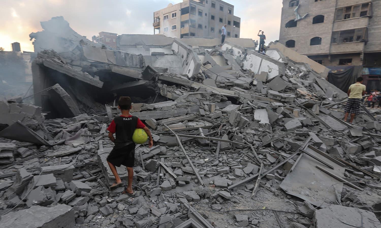 فلسطینی بچہ حملے میں تباہ ہونے والی عمارت کے ملبے کو دیکھ رہا ہے — فوٹو: اے ایف پی
