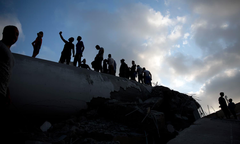 اسرائیل کے  فضائی حملے کے بعد ملبہ ہٹایا جارہا ہے — فوٹو: اے پی