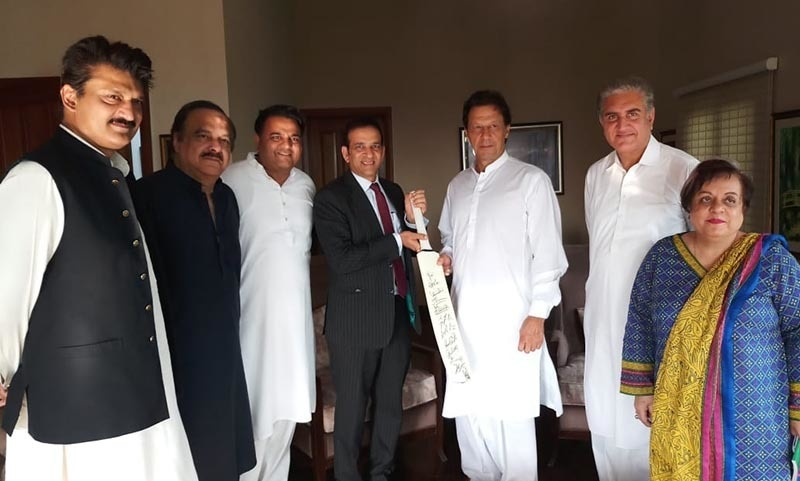 Bisaria presents Khan with a bat signed by Indian cricketers — Photo by author