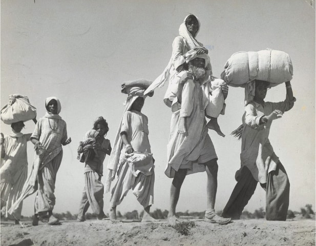 Too weak to walk on her own, a woman sits on her husband's shoulders as Sikhs and Hindus brave the unforgiving October heat during their migration to eastern Punjab from Lahore | Dawn file photo/ Witness to Life and Freedom, Roli Books, Delhi
