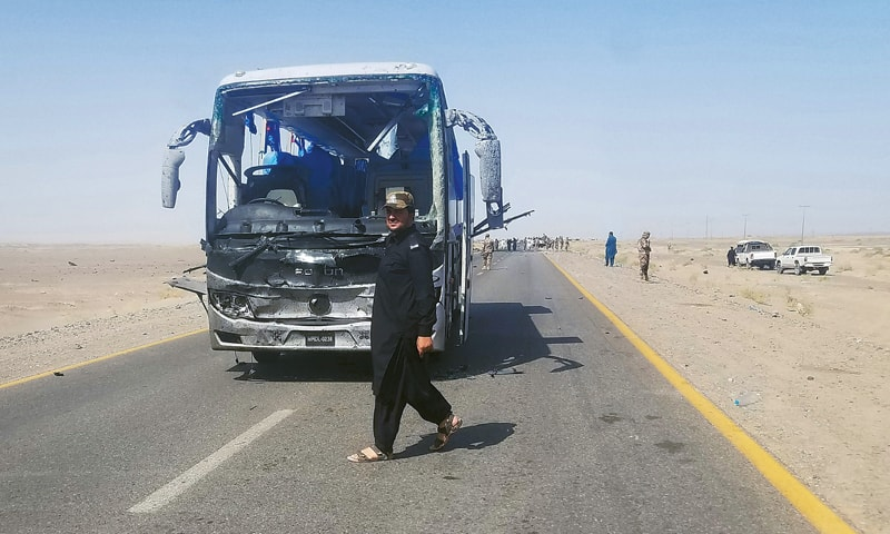 A SECURITY man walks next to a damaged bus carrying Chinese engineers after a suicide attack in Dalbandin region, around 300km from Quetta, on Saturday. The banned Balochistan Liberation Army claimed responsibility for the attack in which three Chinese engineers and two Pakistanis were injured.—AFP