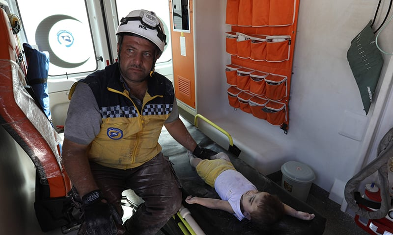 A Syrian rescue worker, part of the White Helmets team, sits next to the body of a baby inside an ambulance on August 12, 2018. —AFP