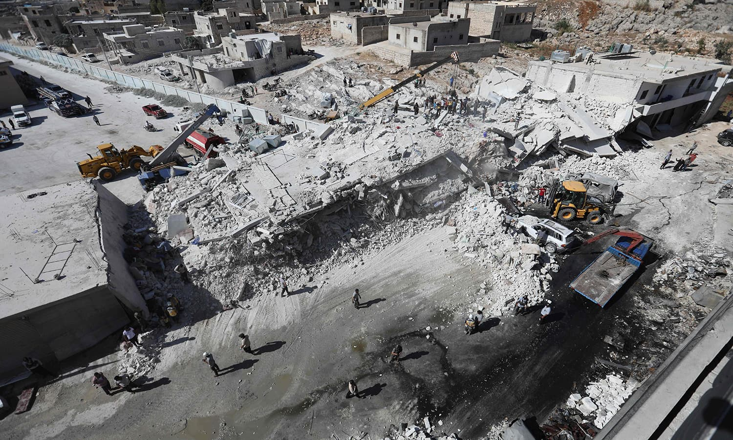 Destroyed buildings are seen on August 12, 2018 following an explosion at an arms depot in a residential area in Syria's northern Idlib province city of Sarmada. —AFP