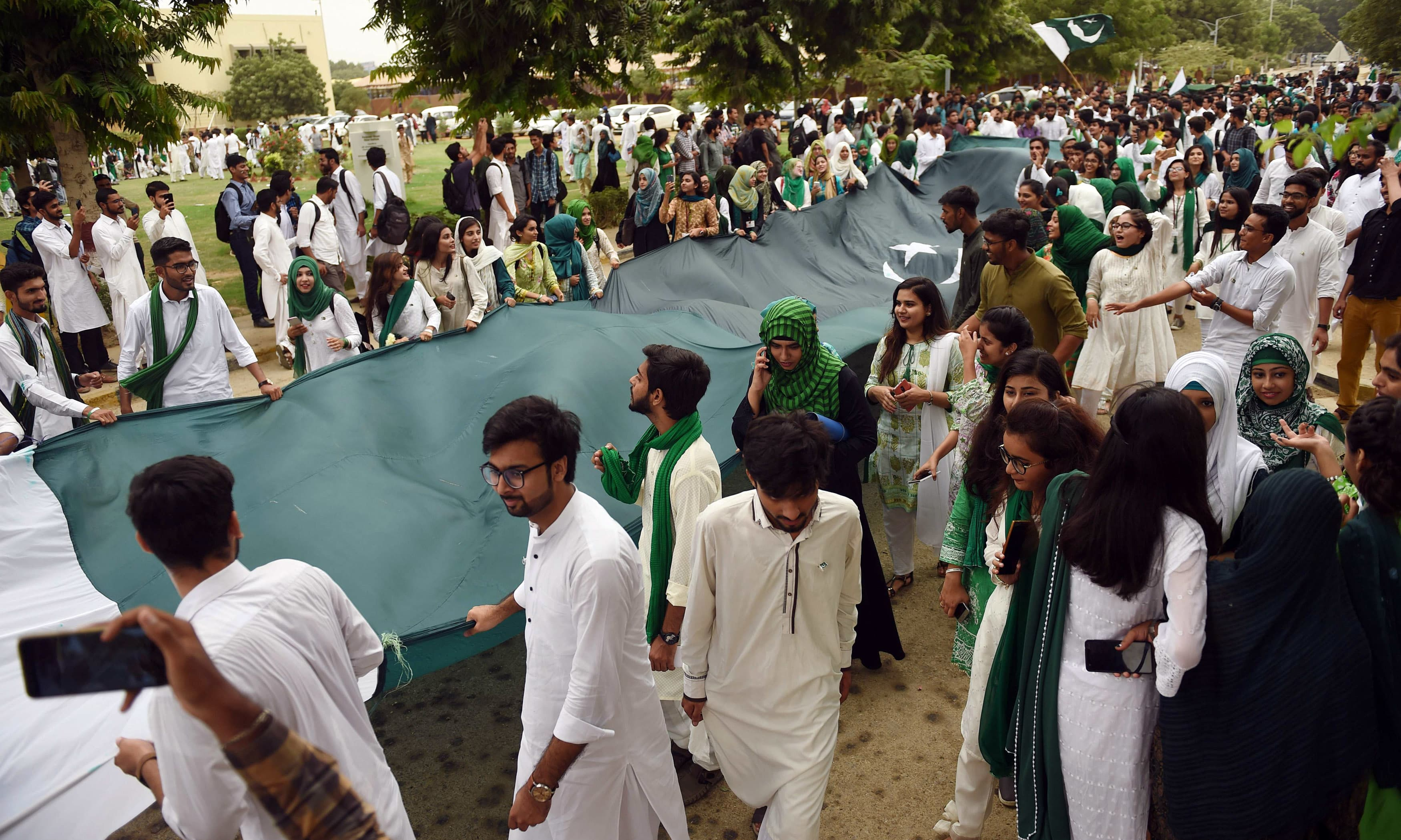 Karachi University students celebrate ahead of the upcoming Independence Day in Karachi. —AFP