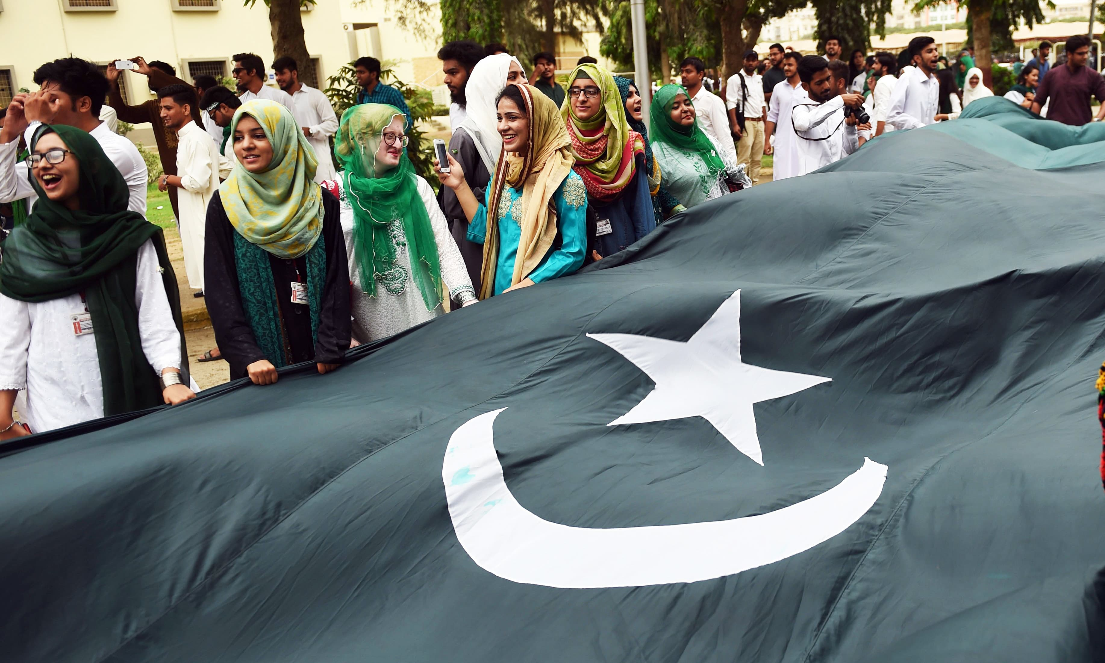 Karachi University students celebrate as they rally while holding a large national flag. —AFP