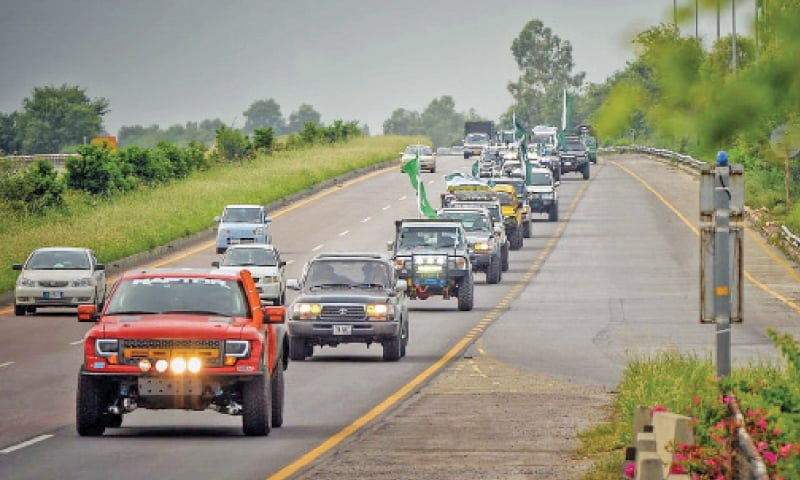 The Azadi March motorcade passes through the motorway on Monday. The rally was organised by KP Tourism Corporation in connection with Independence Day celebrations. — Dawn