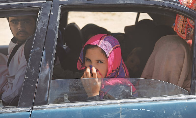 MAIDAN SHAR: An Afghan family, which escaped from the volatile city of Ghazni, photographed in Maidan Shar, west of Kabul, on Monday.—AP