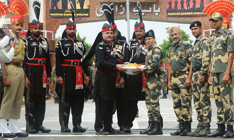 Pakistan Wing Commander Bilal (4L) presents sweets to Indian BSF Commandant Sudeep (4R) at the India-Pakistan Wagah border post on Tuesday. — AFP