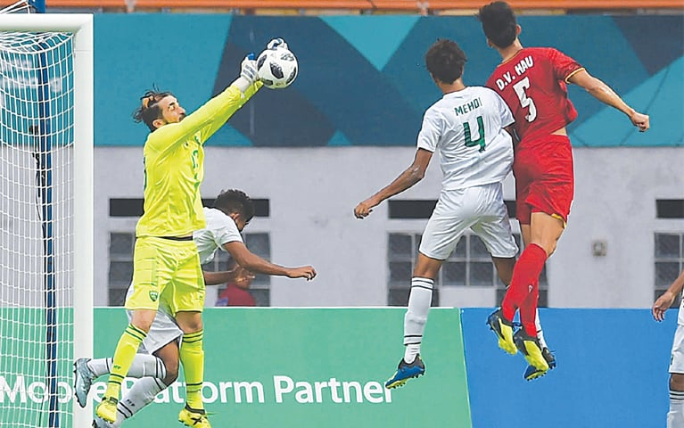 CIKARANG: Pakistan goalkeeper Saqib Hanif punches the ball during the Asian Games Group 'D' match against Vietnam at the Wibawa Mukti Stadium on Tuesday.—AFP