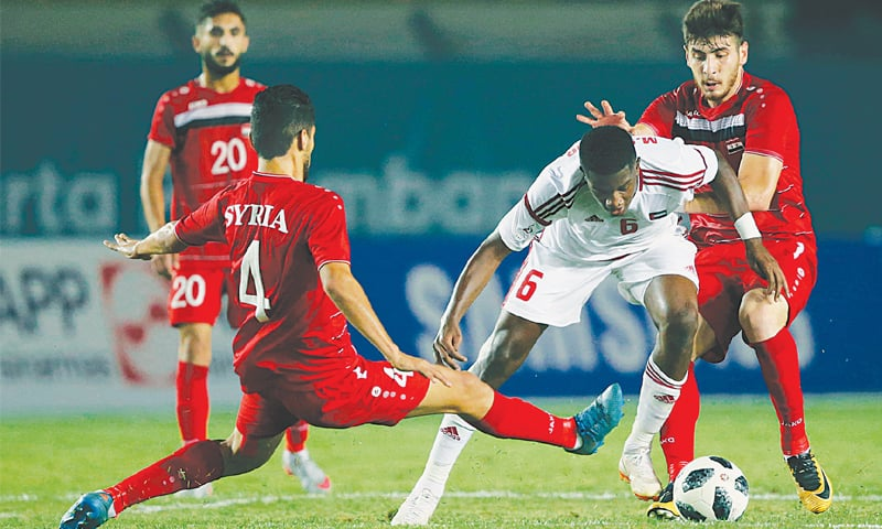 BANDUNG: Ahmed Algheilani (C) of the UAE battles for the ball with Syria's Jihad Busmar (L) during their Group 'C' match at the Si Jalak Harupat Stadium on Tuesday.—AP