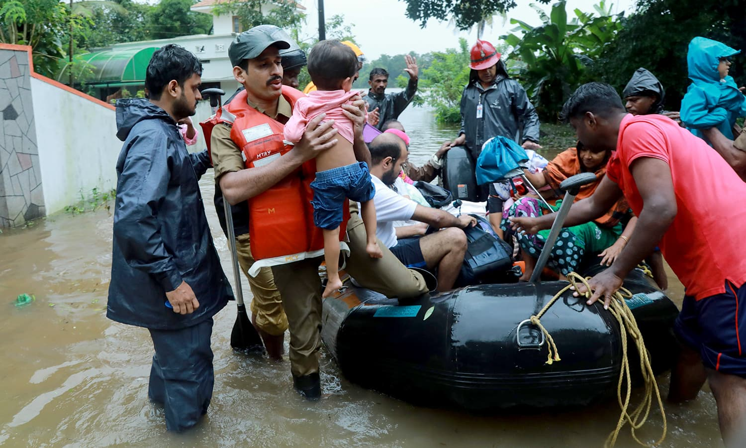 Fire and Rescue personnel evacuate local residents in an inflatable boat from a flooded area. —AFP